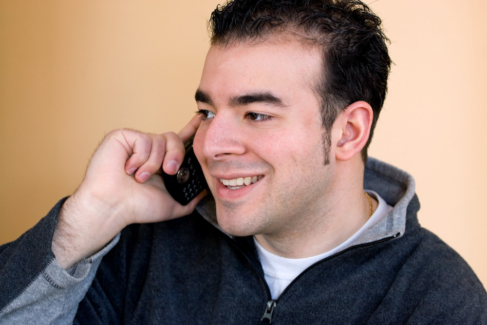 A happy young man having a conversation on his cell phone.