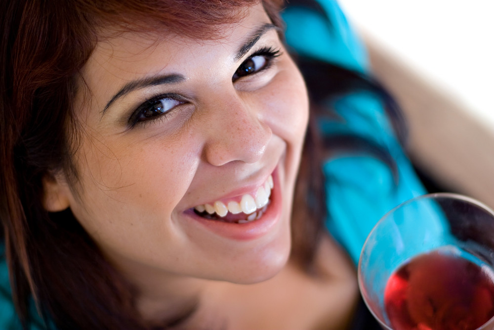 A happy young woman holding a glass of red wine.  Shallow depth of field.