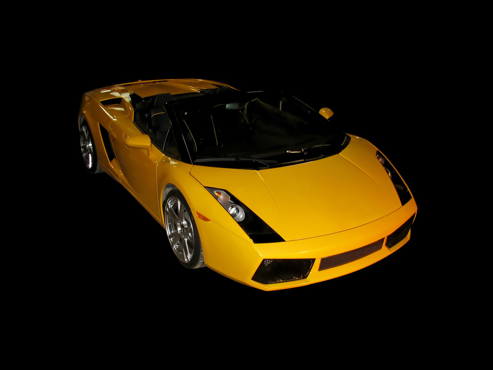 A hot yellow sports coupe over a black background.