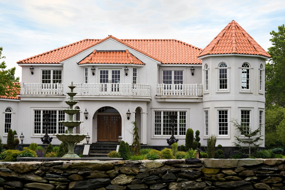 A large mansion with classic architecture and a clay tile roof.