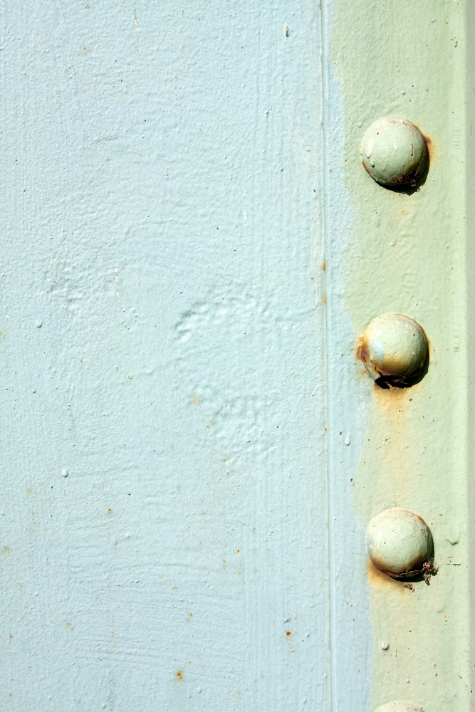 A light green painted metal background texture with three rusted bolts or rivets.