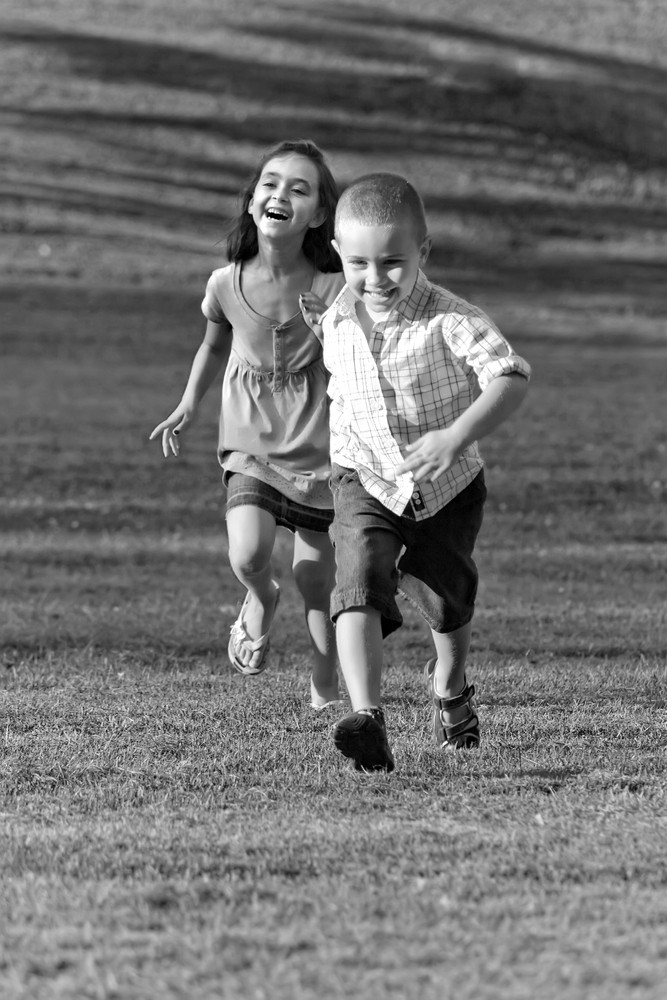 A little boy and girl laughing and running through the grassy field in black and white.