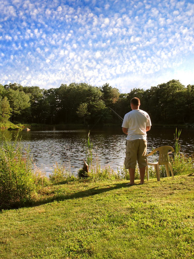 A lone fishermen fishing in a rural pond.
