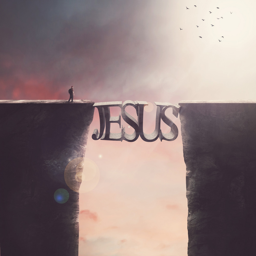 A man approaches a bridge in the shape of JESUS