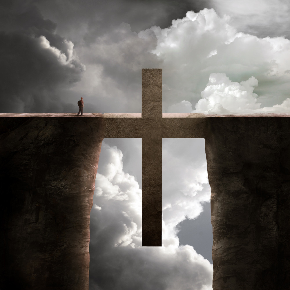 A man crosses over the bridge shaped as a cross