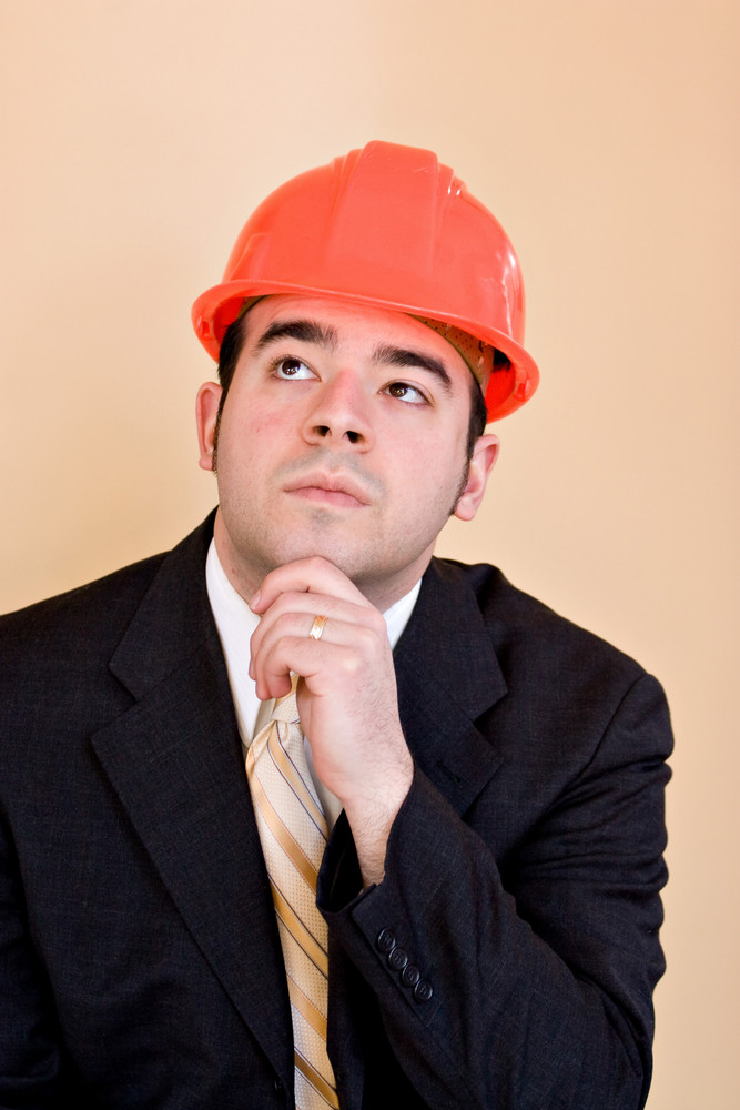 A man in a business suit and hard hat thinking about something. He could be a custom home builder or even an engineer or architect.