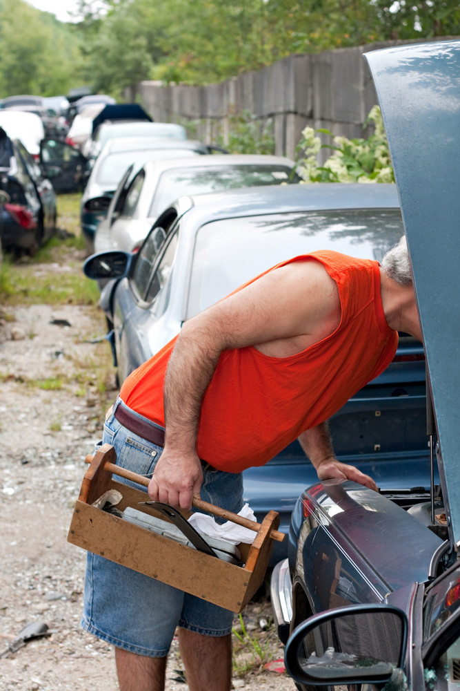 A man looks for car parts under the hook of a decommissioned junk car at an automotive recycking yard.