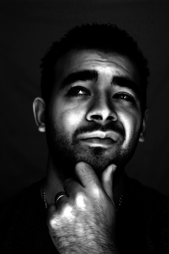 A man with his hand on his chin thinking an important decision - high contrast black and white.
