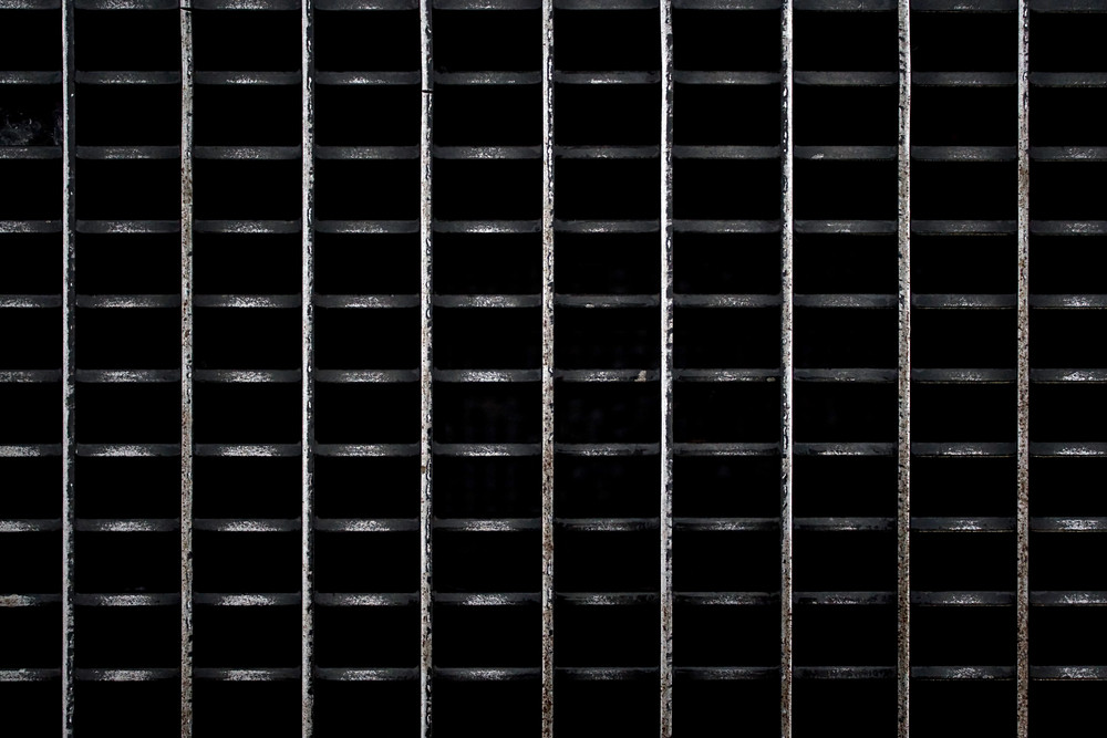 A metal subway grate texture that is worn and weathered.