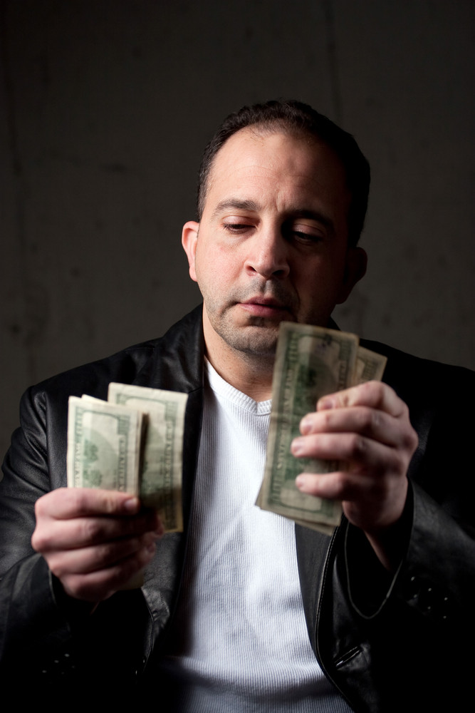 A middle aged man counting a handful of one hundred dollar bills. Shallow depth of field with focus on the face.