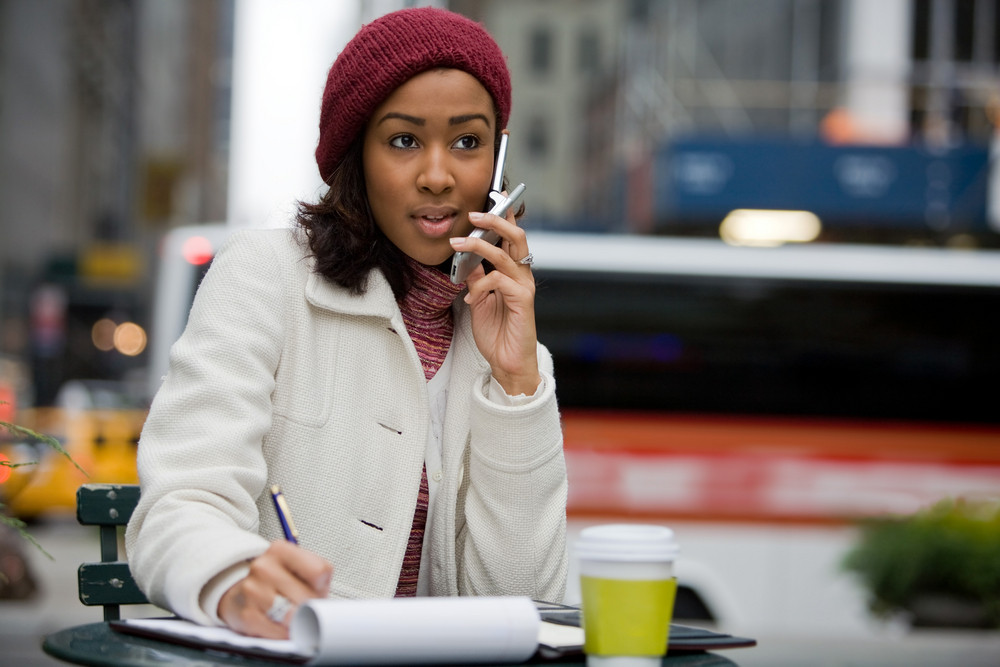 A mobile business woman in the city talks on her cell phone while writing something down in her notepad.