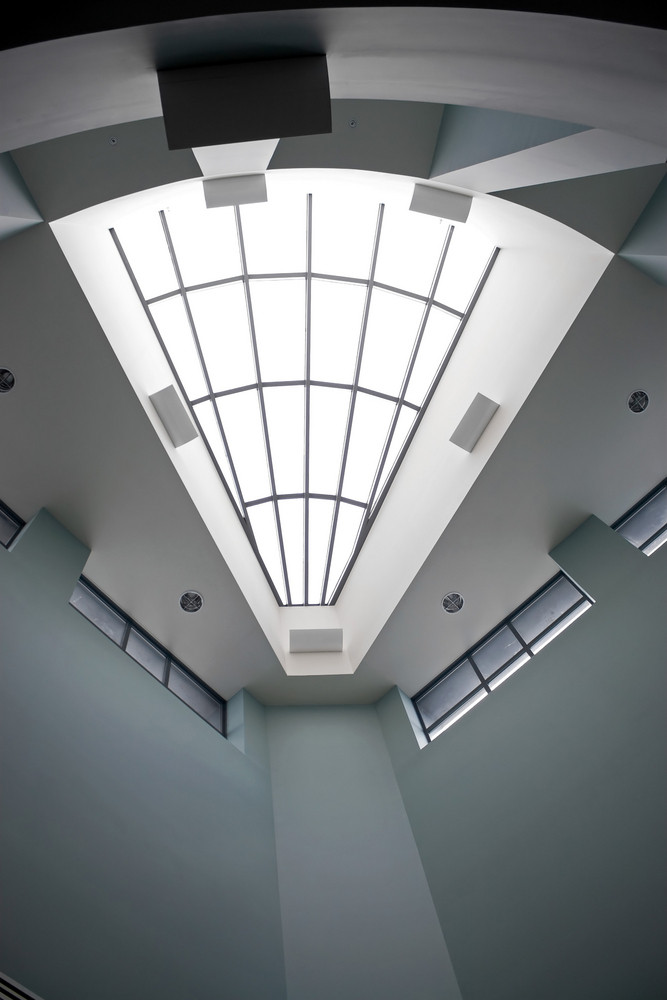 A modern architectural interior with a triangular shaped skylight.