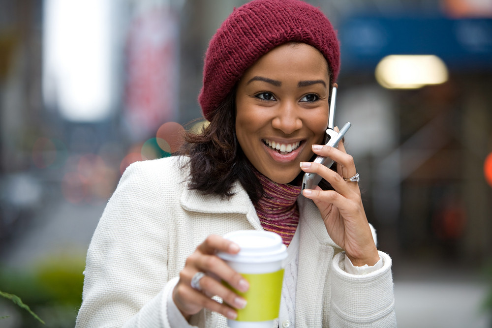 A modern business woman in the city talks on her cell phone while enjoying a cup of coffee.