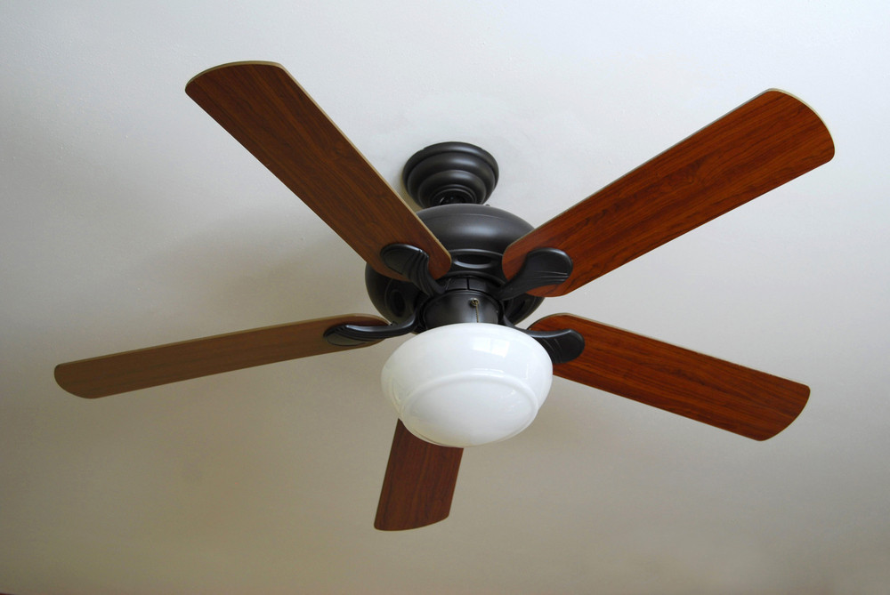 A modern ceiling fan, installed on a textured white ceiling.