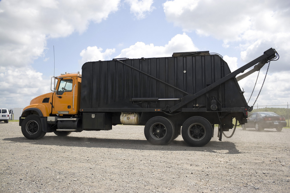 A modern garbage truck over a bright blue sky.
