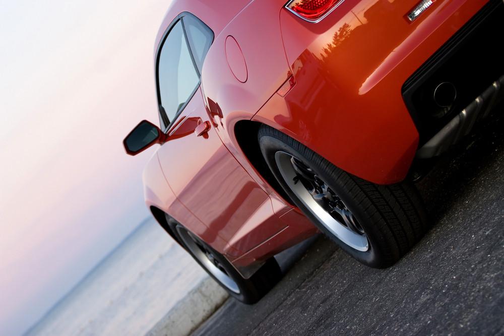 A modern sports car parked at the beach around sunset.
