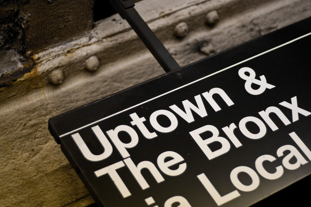 A New York City subway sign pointing to Uptown and The Bronx.