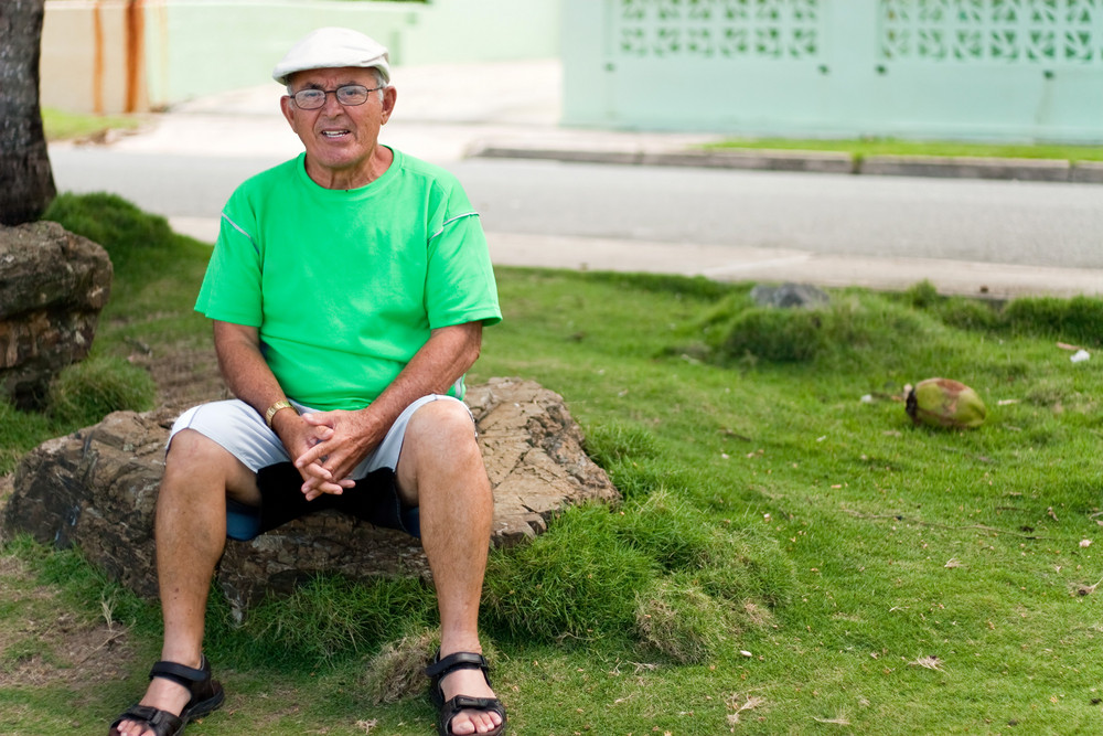 A older Hispanic senior citizen man sits outdoors in a tropical setting.