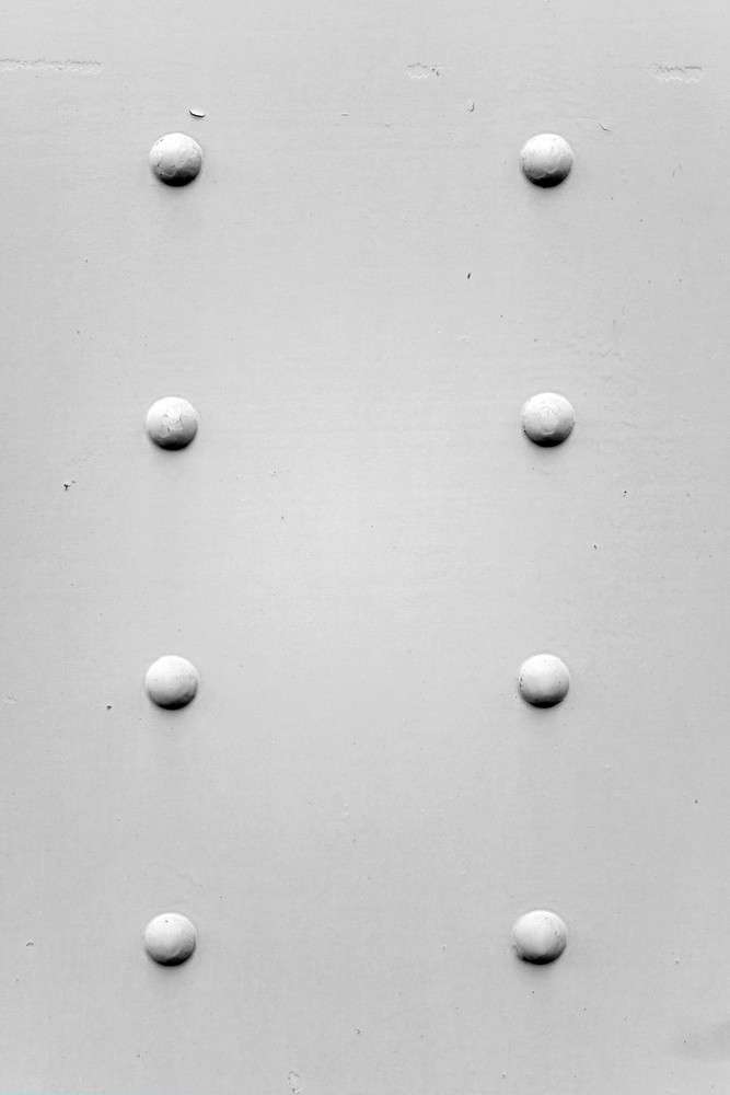 A painted metal background texture with four rusted bolts or rivets in black and white.
