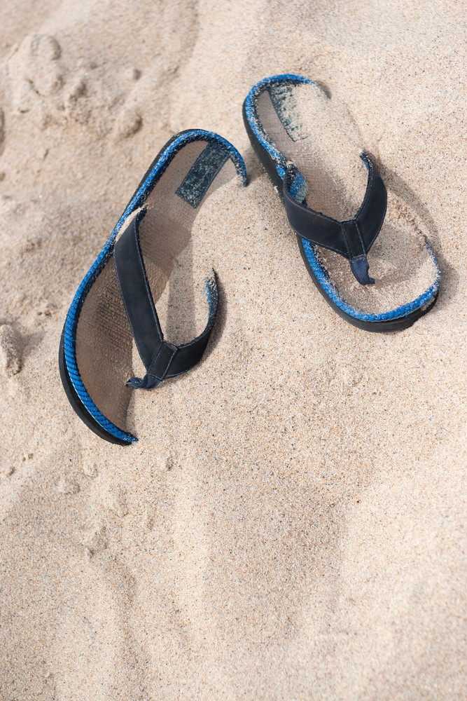 A pair of flip flops or sandals buried in the sand at the beach.