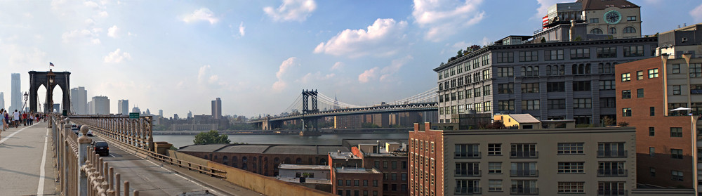 A panoramic image of the New York City skyline including the Brooklyn bridge the Manhattan bridge with the Empire State building in the far distance.