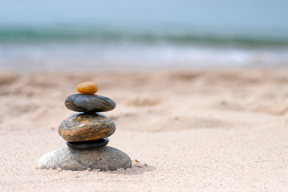 A pile of round smooth zen rocks stacked and balancing in the sand at the beach.