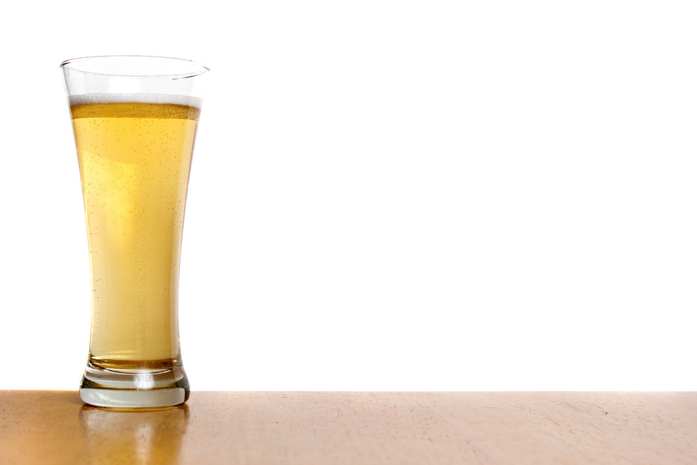 A pilsner glass filled to the top with fresh beer isolated over white.
