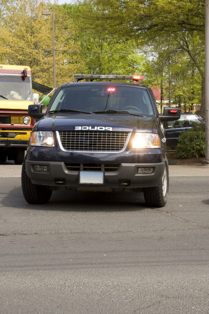 A police sport utility vehicle parked with lights flashing.  Plenty of copy space.
