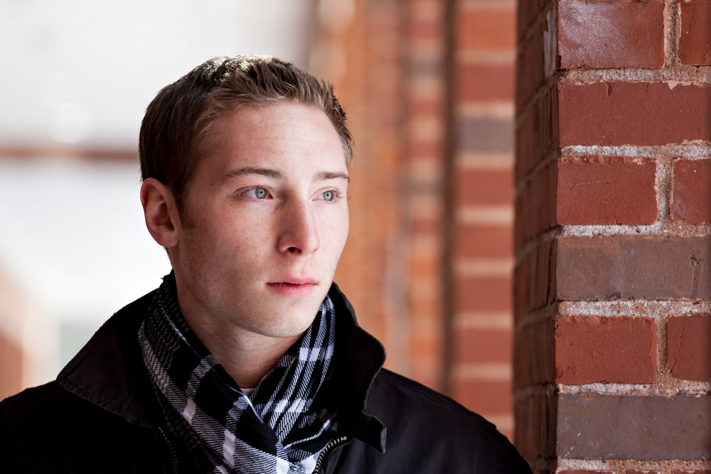 A portrait of a young man standing in an outdoor corridor during winter.