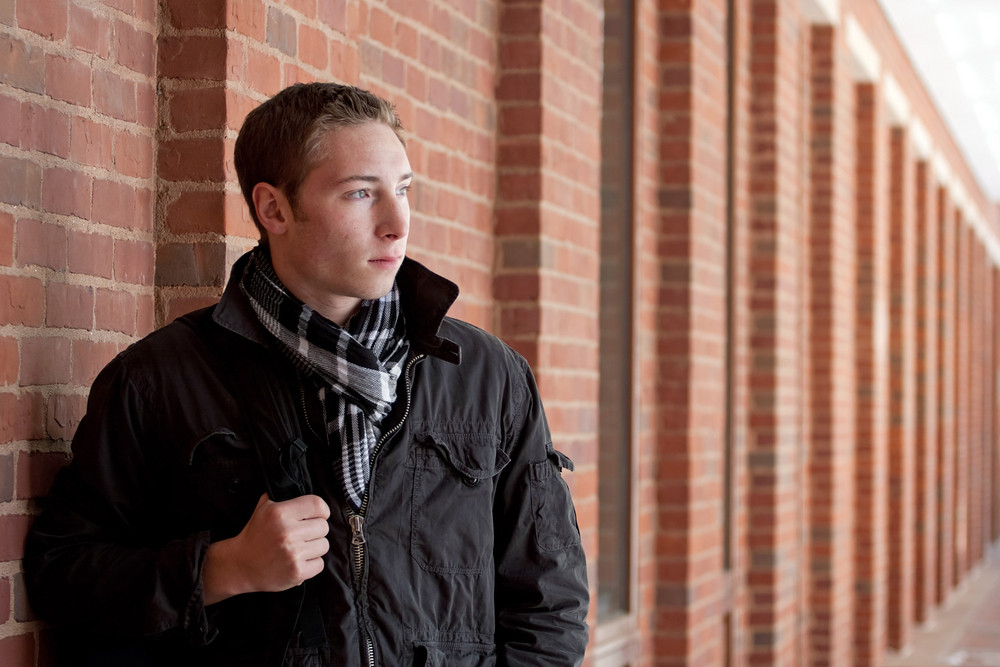 A portrait of a young man standing in an outdoor corridor with his backpack.
