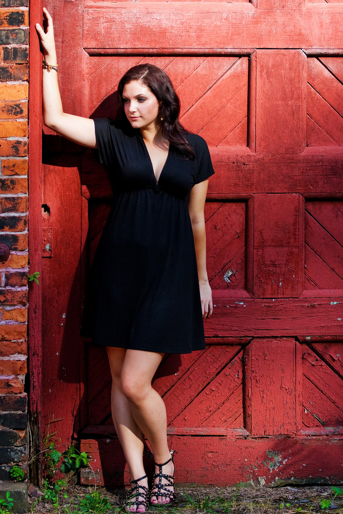 A pretty young woman in a black dress leaning against an old red doorway.