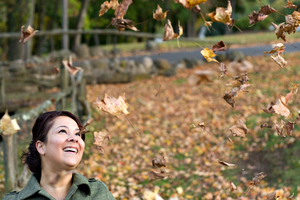 A pretty young woman laughing as the leaves fall all around her during the autumn season.