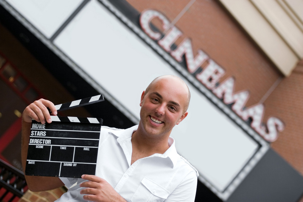 A production assistant or movie director holding a clap board or slate in front of the cinemas.