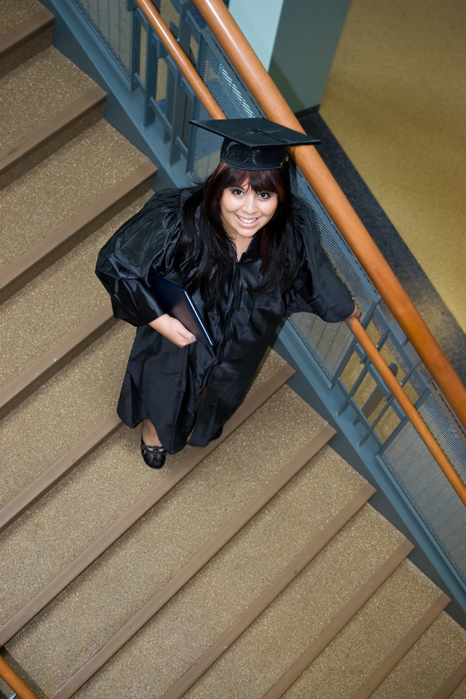 A recent graduate poses on a stairway with her diploma in hand.