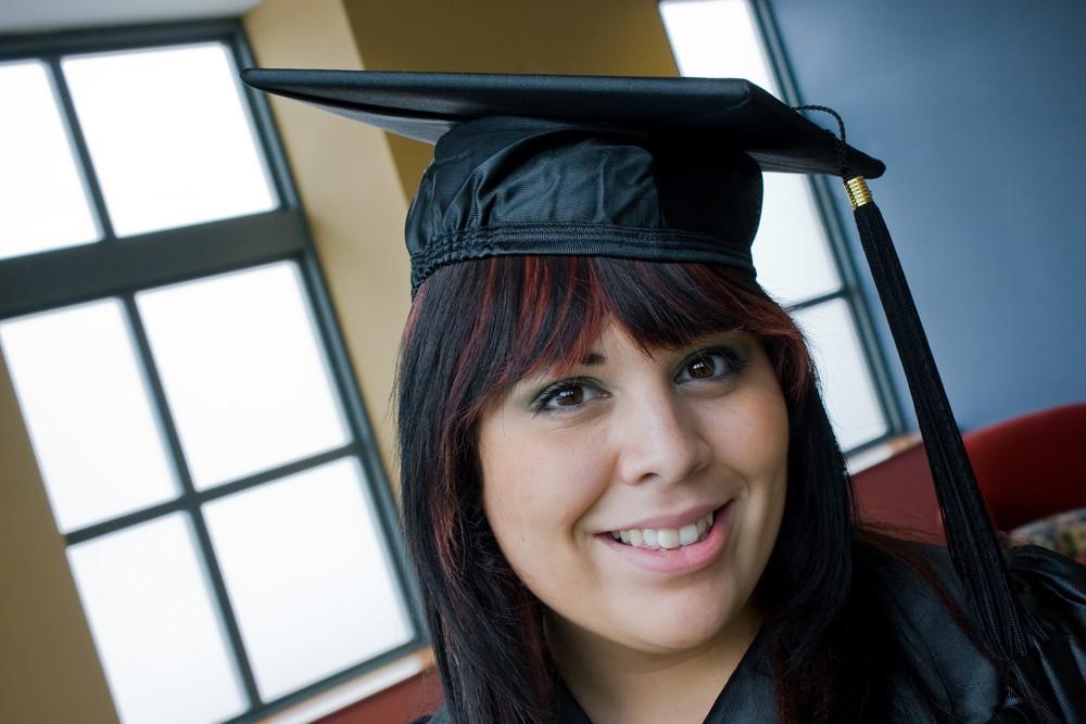 A recent school graduate posing in her cap and gown indoors.