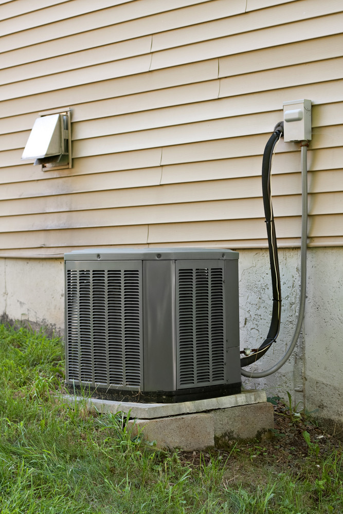 a residential central air conditioning unit sitting outside a home - Central Air Conditioning Unit