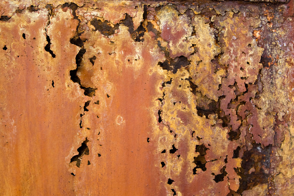 A rotted metal panel covered in rust.