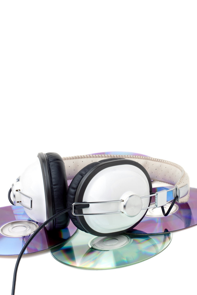 A set of stereo headphones laying on top a pile of compact discs isolated over white.
