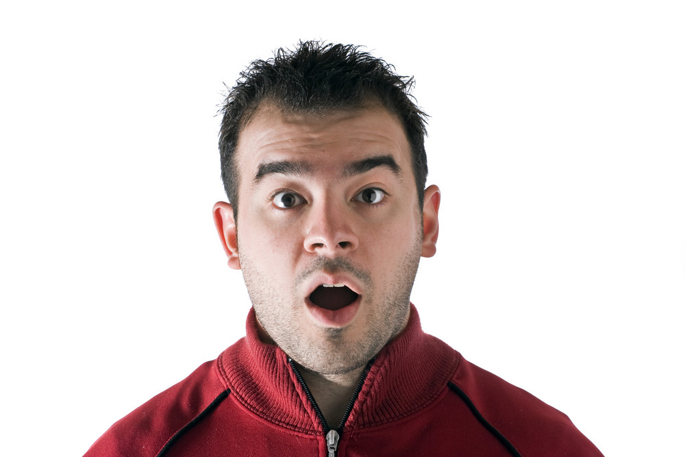 A shocked or surprised young man isolated over white.