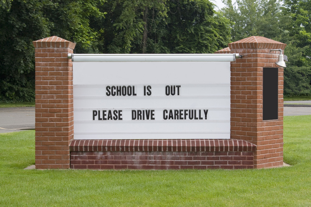 A sign on the town green informs drivers to drive carefully since school is out.  Easily add your own message.