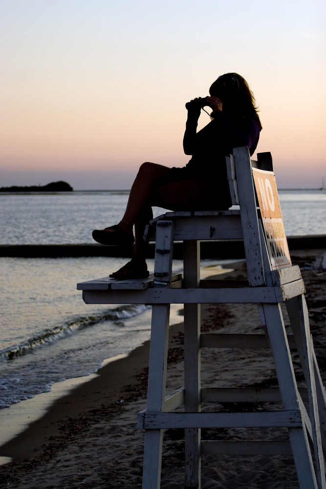 A silhouette of a woman looking with binoculars at the beach while seated in a lifeguard chair.