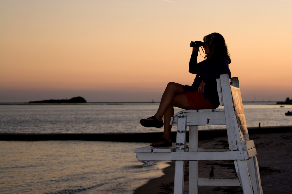 A silhouette of a woman looking with binoculars at the beach while sitting on a lifeguard chair.