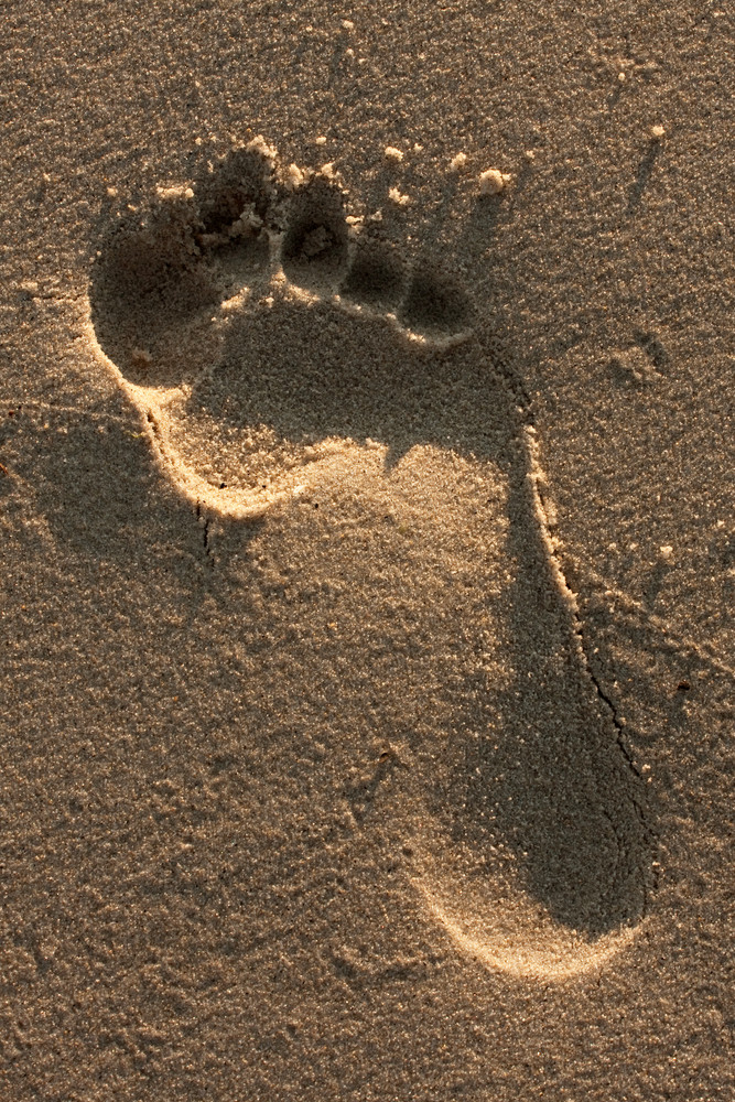 A single foot print imprinted in the sand on the beach.