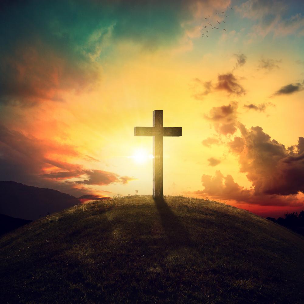A single wooden cross on a hillside at sunset