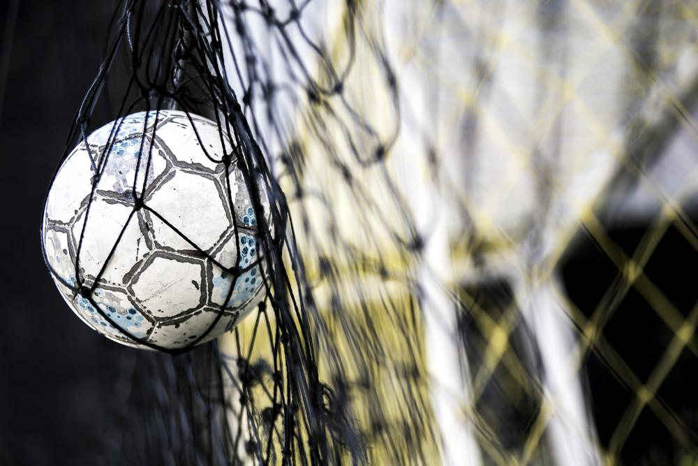 A soccer ball stuck on the net behind goal