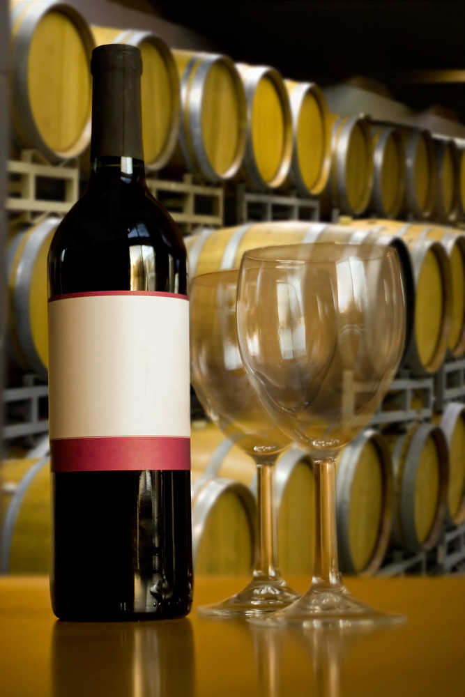 A still life shot of a single wine bottle and a pair of empty glasses in front of some stacked wine barrels.  Shallow depth of field.