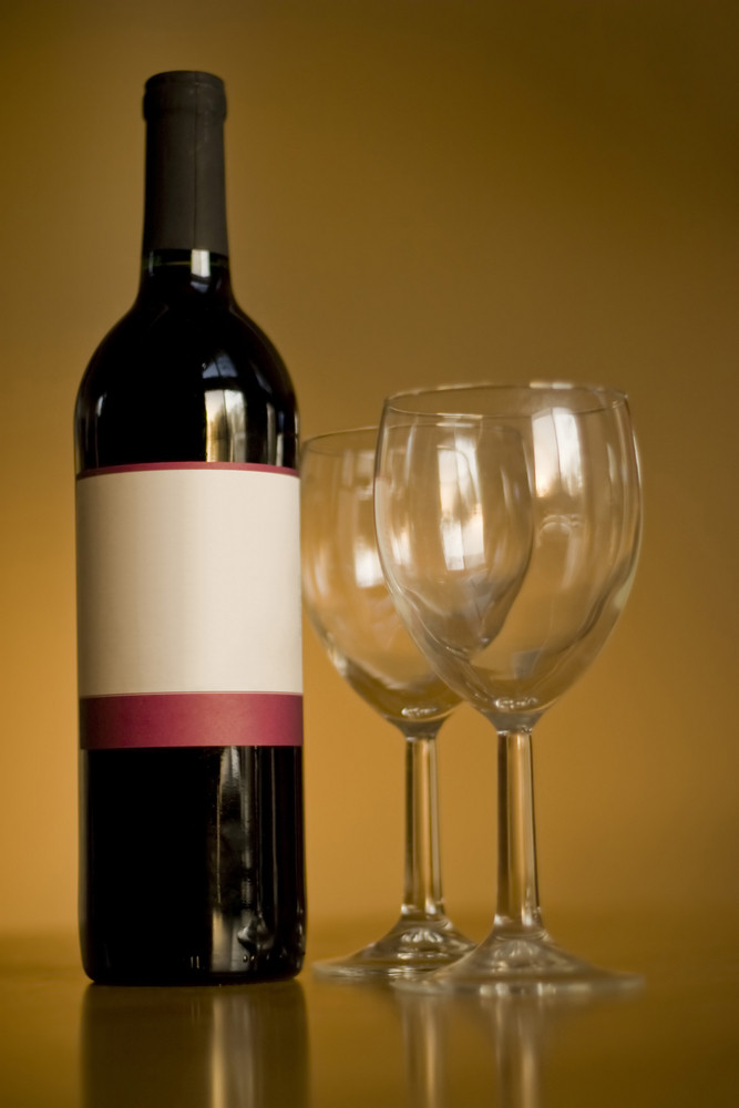 A still life shot of a single wine bottle and a pair of empty glasses.  The label provides copy space for any logo or type desired.