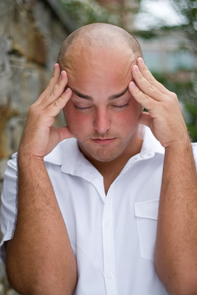 A stressed out young man grabs his head in annoyance from stress or a headache.