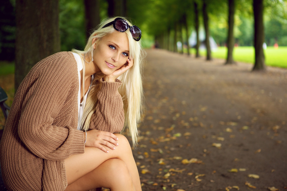 A stylish glamorous blonde woman sits in an empty tree-lined park avenue enjoying the peace and solitude.