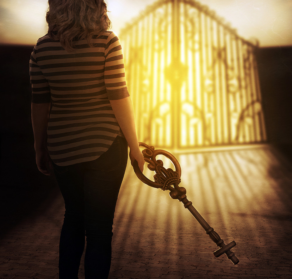 a woman carries a cross shaped key to gates of heaven royalty free